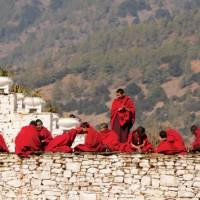 Bhutanese monks socialise along the monastery wall | Liz Light